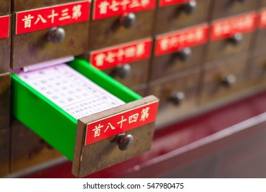 """divination poetry, oracle poetry, fortune slips in drawer, Chinese words """"number eighty four"""" and other numbers on front panels."""