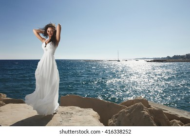 Divine, gorgeous bride standing and posing on the shoreline under summer sun. Marvelous white dress and windy flying cloth.