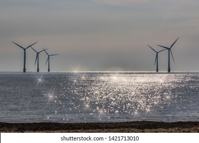 Divine light spiritual image. New age alternative lifestyle of green renewable energy. Offshore wind farm turbines silhouetted on the horizon. Beautiful seascape spiritual background image.