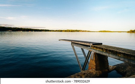 Diving board in stockholm archipelago at sunrise over water