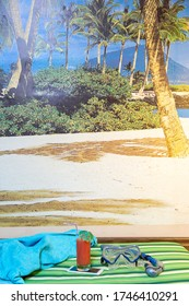 diving galsses and snorkel, glass of tropical juice with cocktail umbrella, blue towel on green striped beach cover. image of sandy beach with palms and blue sky in background in room