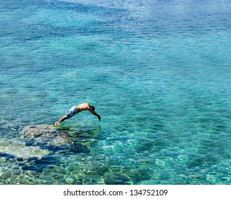 Diving into the sea.
