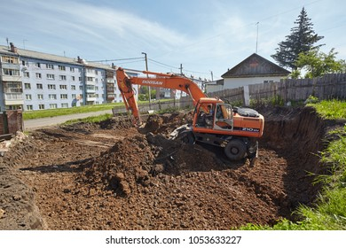 Divnogorsk, Russia - June 16: Construction of a house, preparation of a trench with the technics in Divnogorsk, Russia on June 16, 2017