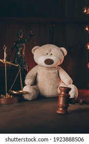 Divorce and alimony concept. Wooden judge gavel and teddy bear in notary public office. Vertical image