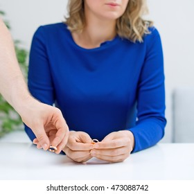 Divorce concept. Man returning wedding ring to his wife.