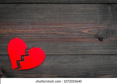 Divorce concept. Sign of divorce. Broken paper heart on dark wooden background top view copy space