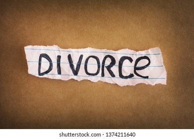 Divorce. Crumpled piece of paper with the word Divorce on brown paper background. Close up.