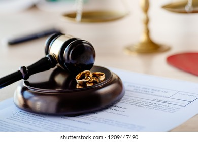Divorce decree in and two broken wedding rings on judge gavel. Divorce and separation concept