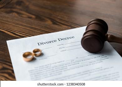 divorce decree, wedding rings and judge hammer on wooden table