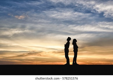 Divorce family - Silhouette of Shadow couples. Women dispute with man about disagreement in young married couples. Anger young couple having quarrel. lover standing opposite in the sunset background.