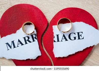 Divorce and separation concept. Two broken golden wedding rings on broken red heart.