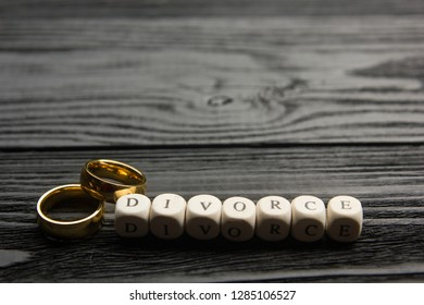Divorce and separation concept. Two golden wedding rings on wooden backgroubd black