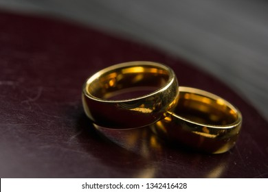 Divorce and separation concept. Two golden wedding rings, judge gavel.
