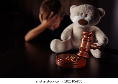 Divorce and separation concept. Wooden gavel, rings and sad little boy with teddy bear. Family law
