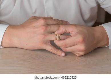 Divorce, separation: man removing wedding or engagement ring