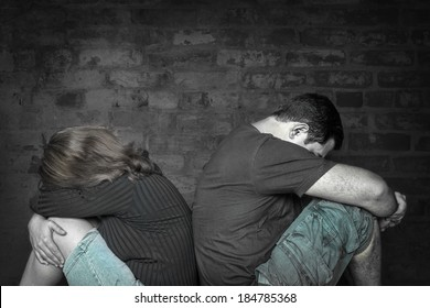 Divorce,problems - Young couple angry at each other sitting back to back with a bricks wall background