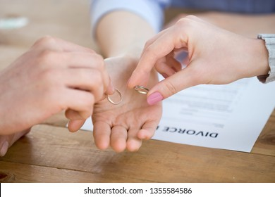 Divorcing family couple give wedding rings to attorney. Process of signing divorce decree. Betrayal, no family, divorced people, relationship crisis, break up, conflict, dead end concept, close up