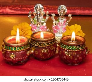 Diwali Background Showing Lit Lamps Against Hindu Idols of Deities Lakshmi and Ganesh