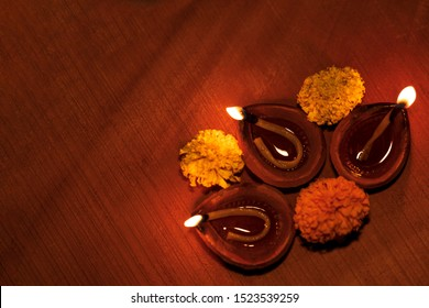 Diwali celebration background top view image with copy space. Beautiful decorative Diwali lamp or diya on wooden surface. Happy diwali greeting card with space for text.