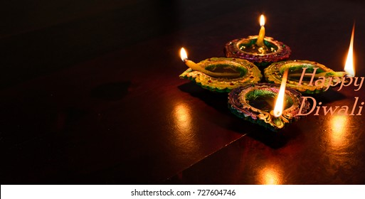 Diwali decorations with traditional Indian oil lamps with selective focus on a wooden table. Both foreground and background are blurry.