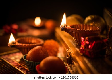 Diwali diya or lighting in the night with gifts, flowers over moody background. Selective focus