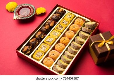Diwali Diya, Sweets OR Mithai and Gift boxes arranged over decorative background. Selective focus