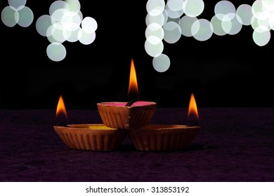 Diwali diyas with bokeh background , Three colorful diya with colored liquid like pink , yellow and orange are placed on to each other like a triangle shape