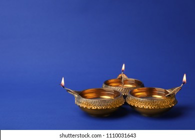 Diwali diyas or clay lamps on color background