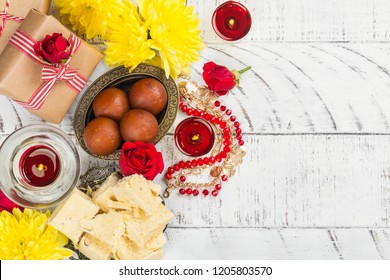 Diwali festival background with flowers, traditional sweets and candles