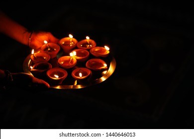 Diwali or festive of lights. Traditional Indian diwali  festival, woman in sari hands holding oil lamp, with defocus light background.