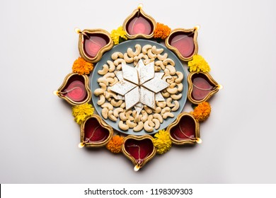 Diwali food Rangoli using Kaju Katli sweet along with Clay diya/lamp and marigold flowers arranged in circular pattern, selective focus
