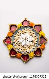 Diwali food Rangoli using Kaju Katli sweet along with Clay diya/lamp and marigold flowers arranged in circular pattern, selective focus