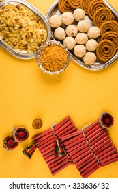 diwali greeting card - food / snacks /sweets with fire crackers in silver plate isolated over decorative background