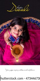 Diwali Greeting Card showing Cute little indian/asian girl in traditional wear holding a diya or Terracotta oil lamp. top view over black background