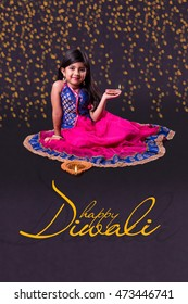Diwali Greeting Card showing Cute little indian/asian girl in traditional wear holding a diya or Terracotta oil lamp. Front view over black background