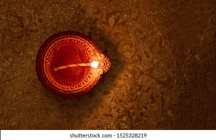 Diwali, Hindu festival of lights. Clay diya candle illuminated in Dipavali. Oil lamp on traditional tray, copy space.
