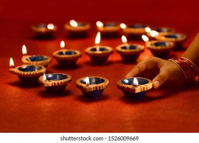 Diwali lamp lit by hand, Diwali Lamps , Diwali diya lamps lit during diwali celebration