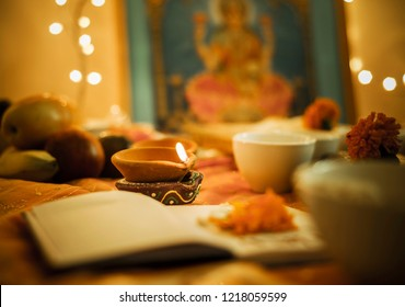 Diwali puja set up. Selective focus on burning traditional earthen lamp surrounded by an elaborate Laxmi puja.