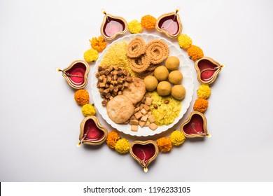 Diwali Rangoli or design made using Indian snacks/sweet and diya or lamp and flowers