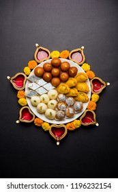 Diwali Rangoli made using Diya/oil lamp, flowers and plate full of Gulab Jamun, Rasgulla, kaju katli, morichoor / Bundi Laddu, Gujiya or Karanji
