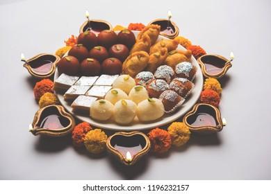 Diwali Rangoli made using Diya/oil lamp, flowers and plate full of Gulab Jamun, Rasgulla, kaju katli, morichoor / Bundi Laddu, Gujiya or Karanji