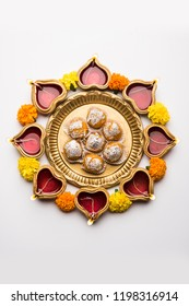 Diwali Rangoli using Diya, flowers and Motichoor Laddu or Boondi Laddoo arranged over white background, selective focus