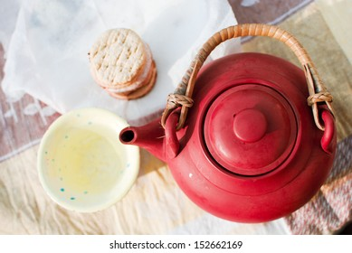DIY ceramic kettle and cup with green tea, outdoor