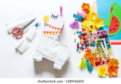 Diy cinco de mayo Mexican Pinata llama made cardboard and crepe paper your own hands on a white background. Gift idea, decor, game cinco de mayo. Step by step. Top view. Process kid children craft.