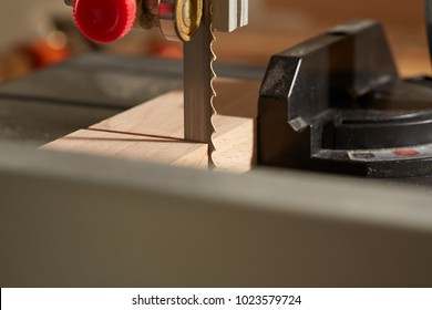 DIY concept. Woodworking and crafts tools. Sawing Hardwood workpiece on the bandsaw