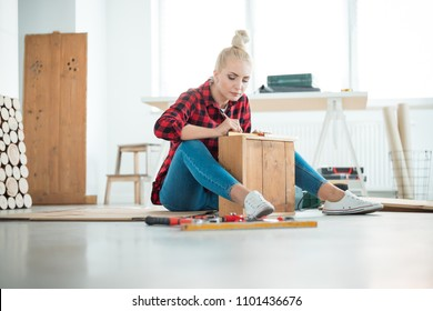 DIY concept. Young woman repairing furniture at home, sitting on the floor.