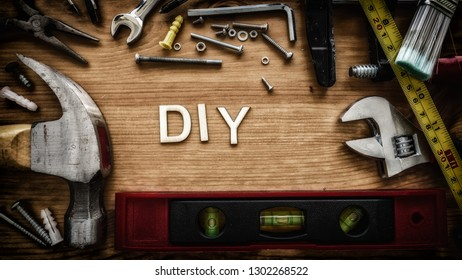 DIY, do it yourself, spelled out with wood letters bordered by various home improvement tools.