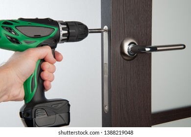 DIY door lock repair. Hand with green drill.