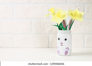 DIY Easter vase bunny from glass jar, felt, googly eyes on a green background. Gift ideas, decor for spring, Easter. Handmade. Step by step. The process of crafts. Top view. Childrens Easter crafts.