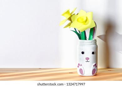 DIY Easter vase bunny with narcissus, daffodils from glass jar, felt, googly eyes on a white wall background. Gift ideas, decor for spring, Easter. Handmade. crafts. Kid Childrens Easter crafts.